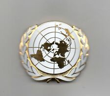 UNITED NATIONS GILT AND ENAMELLED CAP BADGE - IN ORIGINAL SUPPLIERS PACKET