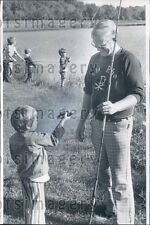 Cute Boy Shows Small Catch of Fish to Adult Fisherman Press Photo