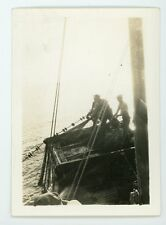 Graphic silhouette of fisherman hauling nets on deck of boat.  Vintage photo
