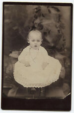 CABINET CARD BABY IN WITH GOWN AND HIGH BUTTON BOOTS. PAINTED BACKGROUND.