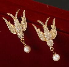 Gold tone crystal swallow bird with a hanging pearl stud earrings