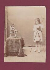 PHOTO ancienne - appareil photo sur pied poupée sur chaise haute - 120615
