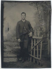 UNMOUNTED TINTYPE, MAN STANDING WITH A LOG FENCE. PAINTED BACKGROUND.