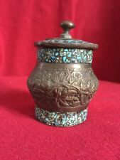 antique copper jar with blue stone on it.