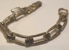 Silver tone chain link bracelet with scroll design and dangle charm