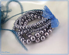 SET OF SIX PRETTY SILVER GREY ACRYLIC BEAD BRACELETS TIED WITH A BLUE RIBBON (G)