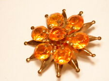 Gold colored starburst fashion pin with large orange colored jewels