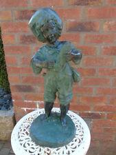 statue en bronze d un garçon avec poisson , jet d eau , étang , fontaine .