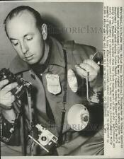 1959 Press Photo Jo Schuppe examines damaged camera equipment - ney23235