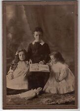 ANTIQUE CABINET CARD PHOTO YOUNG BOY AND 2 GIRLS HOLDING PICTURE BOOK & DOLL