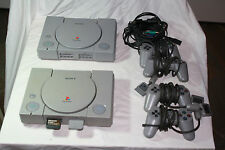 2 x Gray Playstation Consoles, 4 controllers, 2 power cables, 2 memory cards