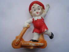C1920S VINTAGE LITTLE BOY RIDING A SCOOTER BISQUE BIRTHDAY CAKE DECORATION