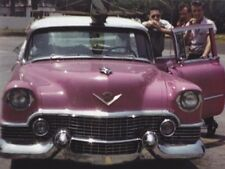 Elvis Presley with the pink Cadillac he used to tour with in the late 1950's.