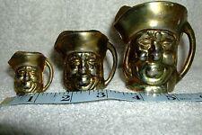 Set of 3 brass toby jugs.