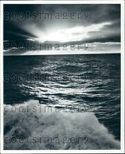 Moonlight Breaking Through Clouds Over Crashing Waves Press Photo
