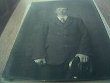 postcard photograph b/w man with hat in hand staring