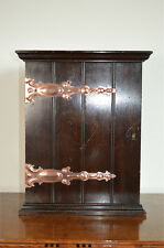 A small Arts and Crafts mahogany cabinet with copper strap hinges