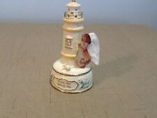 Light house music box. A little hope lights the way. Beige and gold trim .Angel.