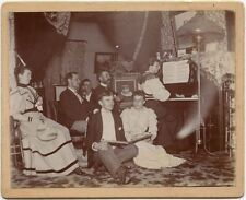GROUP AROUND PIANO WITH SHEET MUSIC CABINET PHOTO