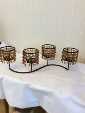 A BROWN METAL STAND WITH 4 TEA LIGHT HOLDERS AND AMBER JEWELS