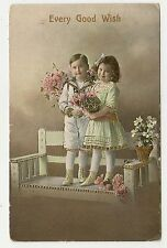 ANTIQUE GREETINGS POSTCARD CHILDREN BOY GIRL STAND BENCH PINK WHITE FLOWERS 1914