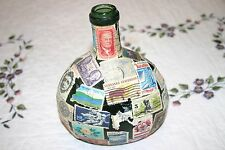 OLD GREEN BOTTLE COVERED WITH VINTAGE POSTAGE STAMPS