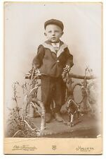 Vintage cabinet card of young boy with toy horse pull toy, on rustic twig bench