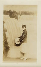 WOMAN WEARING MILITARY JACKET CHASES WATERFALL WITH A BUCKET (VINTAGE RPPC)