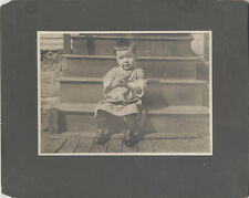 ANTIQUE IMAGE OF YOUNG CHILD SITTING ON THE STEPS OUTSIDE. MOUNTED TO BOARD.