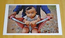 MAGNUM PHOTO POSTCARD ~ TRANSPORTING A CHILD THE TRADITIONAL WAY, CAMBODIA 1998