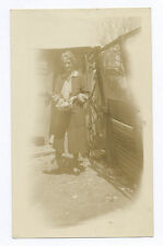 1930's SNAPSHOT: FARM SCENE OF WOMAN WITH BOWL OF ANIMAL FEED