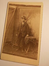 stehender Mann mit Bart im Anzug mit Hut - Kulisse - Tisch / CDV