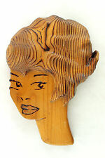 a vintage 1960's carved wall hanging. Lady's head. Stylized retro design.