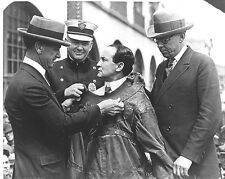 Photo of Harry Houdini is secured in a straightjacket being secured by strangers