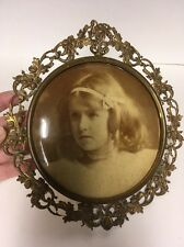 Antique Round Brass Ornate Frame Around Picture Of A Girl On Metal Convex.