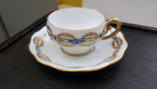 SMALL SHAPED CUP AND SAUCER BY KOENIGSZELT SITESIA WITH A GOLD AND BLUE PATTERN