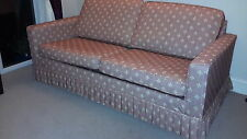 sofa bed with pink loose covers.