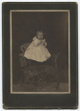 HAPPY LEVITATING BABY, ORNATE CHAIR. EARLY 20TH CENTURY.