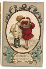 Birthday Greetings a boy and girl sneak a kiss behind a hand muff