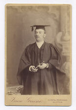 CABINET PHOTO OF GRADUATE, MAN HOLDING A SPYGLASS AND WEARING A MORTAR BOARD HAT