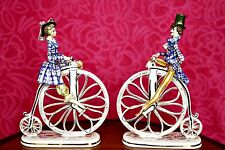A Pair of Man & Women Riding Penny Farthing Bicycle Porcelain Figurines, Italy
