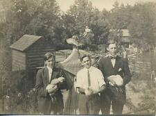 3 Men Holding 3 Live Chickens