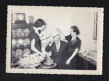 Antique Photograph Women Trying Woman's Hat On Man in Retro Dining Room