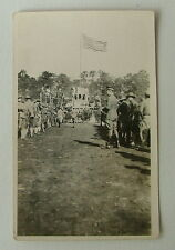 RPPC POSTCARD WWI SOLDIERS MILLING STANDING IN FRONT OF REVIEW STAND & FLAG