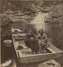 STEREOVIEW COUPLE ON FLAT BOTTOM BOAT, WATERFALLS IN BACKGROUND.