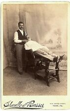A barber shaves a customer on a reclining wood chair. Lot 421