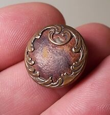 Beautiful Antique Art Nouveau brass button with leather insert background