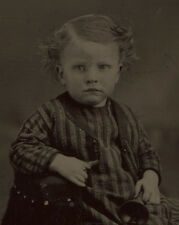 TINTYPE YOUNG CHILD IN STRIPED AND CHECK OUTFIT HOLDING A BELL. TINTED. UNHAPPY.