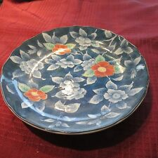 blue decorative plate from japan ; flowers in the pattern on the plate