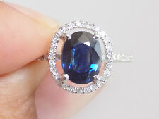 Large natural sapphire and diamond halo engagement ring